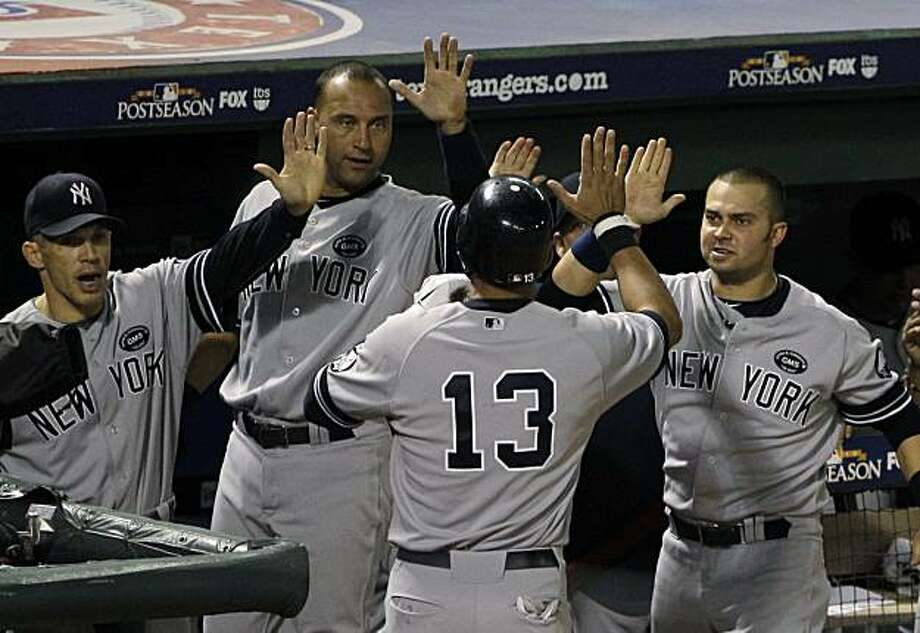New York Yankees' Alex Rodriguez (13) is greeted by manager Joe Girardi, left, Nick Swisher, right, and Derek Jeter after scoring against the Texas Rangers on a single by Marcus Thames in the eighth inning of Game 1 of baseball's American League Championship Series Friday, Oct. 15, 2010, in Arlington, Texas. Photo: Paul Sancya, AP