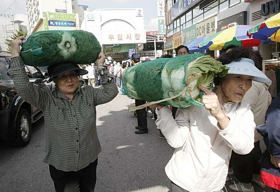 South Korean housewives leave after buying subsidized Napa cabbages at Woorim Market in Seoul, South Korea, Tuesday, Oct. 5, 2010. South Korea is struggling to secure its supply of kimchi _ the spicy, pickled food that serves as the national dish _ afteran unusually long stretch of bad weather spoiled the latest crop of Napa cabbage, its main ingredient. Photo: Ahn Young-joon, AP