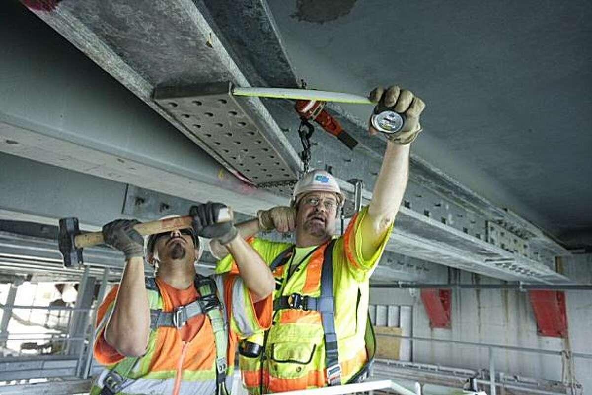 Caltrans workers repair a cracked beam beneath the San Mateo-Hayward Bridge/