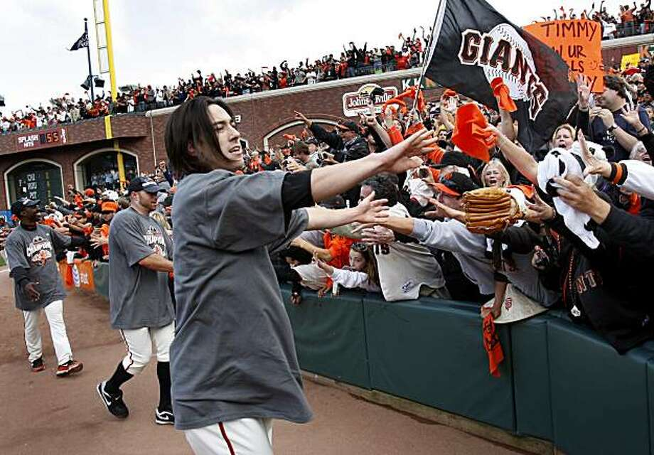 Tim Lincecum (center) is greeted by fans as he runs around the field with other players after the Giants defeated the San Diego Padres to win the National League West championship Sunday. Photo: Brant Ward, The Chronicle