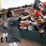 Tim Lincecum (center) is greeted by fans as he runs around the field with other players after the Giants defeated the San Diego Padres to win the National League West championship Sunday.