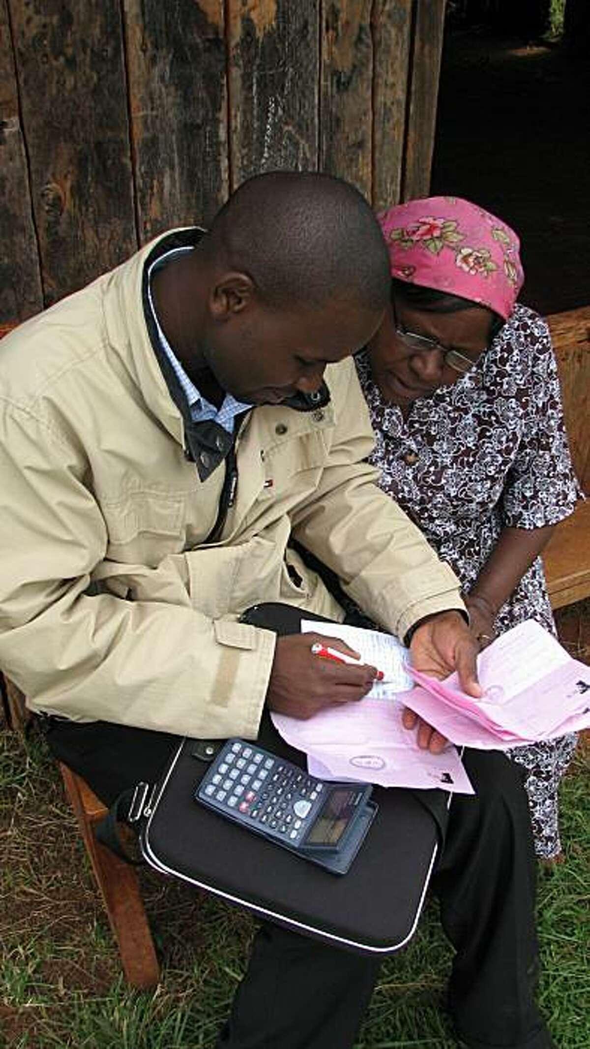 Loan officer John Muigai reviews loan repayments from Kenyan farmer Teresia Njambi for farm equipment through a micro-asset financing program.