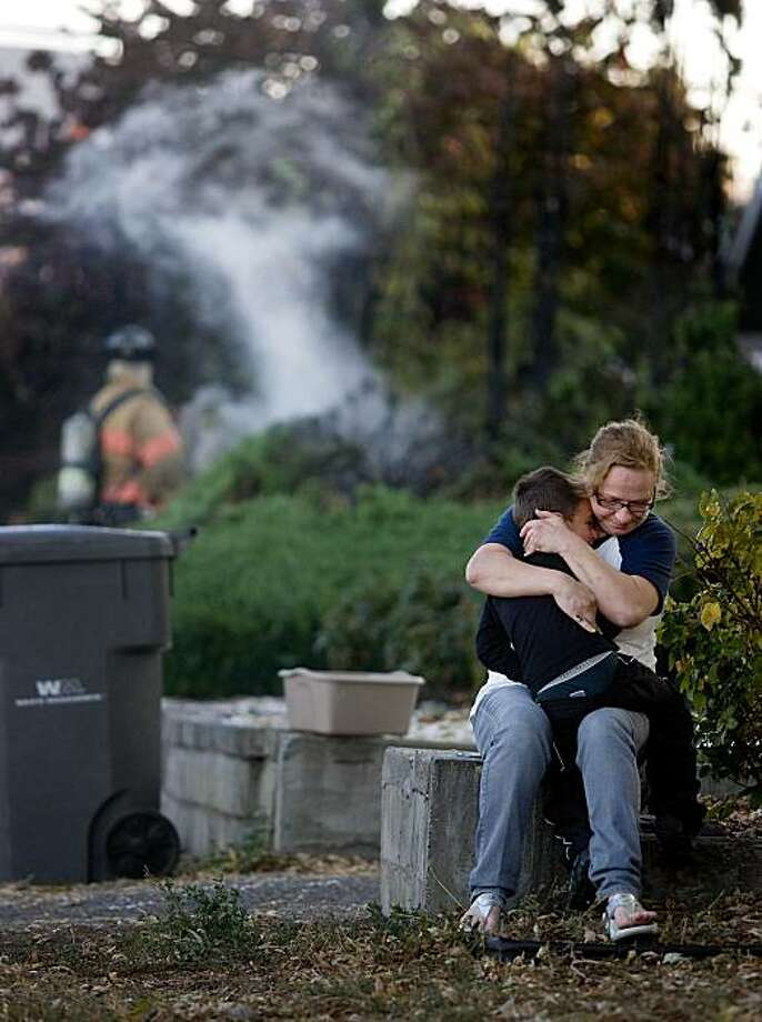 Sarah Stalder comforts her son, Marcus, 6, as a Wenatchee, Wash., firefighter extinguishes a brush fire that burned outside their home in Wenatchee Tuesday, Oct. 12, 2010. The home is owned by Sarah's mother, Ellie Youngman. No one was injured in the fire. Photo: Don Seabrook, The Wenatchee World