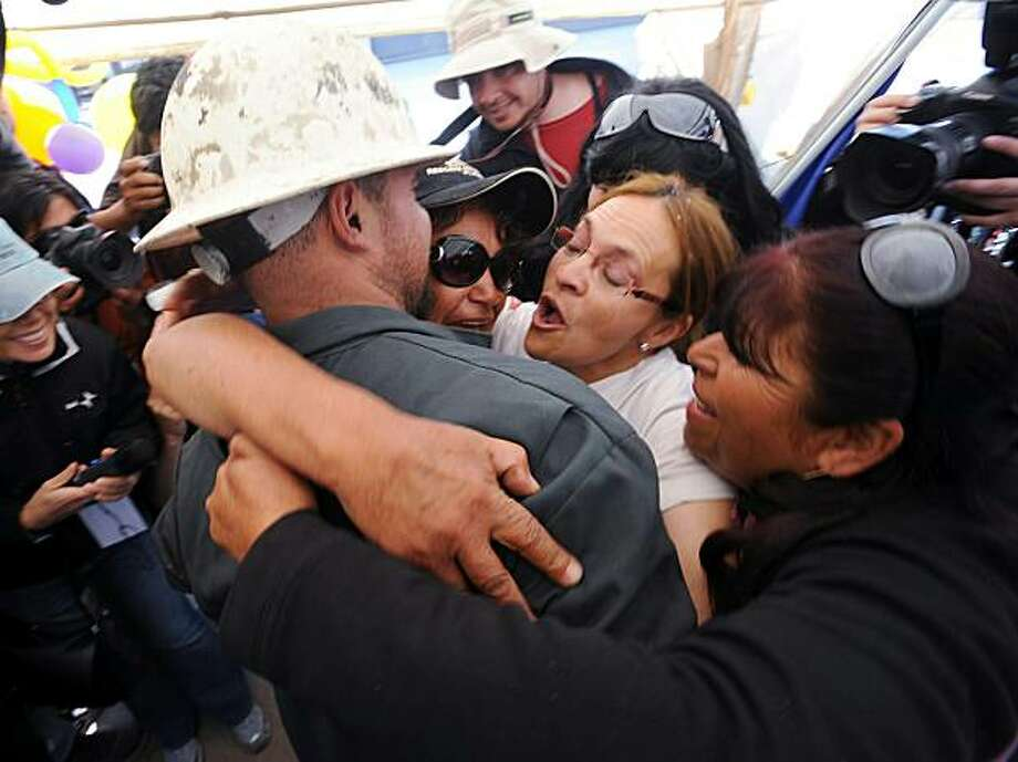 Relatives of trapped miners embrace US drill operator Matt Staffel (L) after the T-130 drill working to rescue the 33 miners finally reached their shelter in the San Jose mine, near Copiapo, Chile on October 9, 2010. After a record two months trapped underground in a collapsed mine, the miners appear to be just days from a miraculous rescue. Photo: Claudio Santana, AFP/Getty Images
