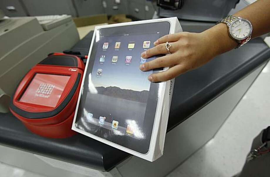 In this Oct. 3, 2010 photo, a customer purchases an a Apple iPad at a Target store in Cupertino, Calif. Apple's shares topped $300 for the first time Wednesday, Oct. 13, as stellar iPad sales and a planned expansion into China continued to give investorshigh hopes for the iPhone maker's already healthy prospects. Photo: Paul Sakuma, AP