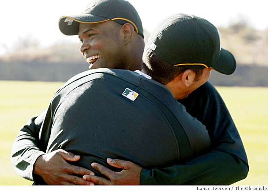 Oakland Athletics catcher Kurt Suzuki back to camera hugs pitcher Santiago Casilla  prior to the start of Spring Training workouts at the Papago Baseball Facility February 14, 2009 in Phoenix Arizona Photo: Lance Iversen, The Chronicle
