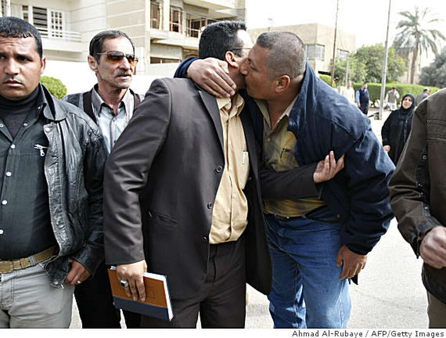 An Iraqi supporter kisses Udai, the brother of jailed journalist Muntazer al-Zaidi, as he leaves the Central Criminal Court in Baghdad on February 19 2009, following the first day of his brother's trial. The 30-year-old Iraqi journalist who threw his shoes at US president George W. Bush went on trial with his lawyers set to argue that the remarkable protest was lawful. Zaidi won global fame when his footwear whizzed past Bush's head on December 14 as the president was making a farewell visit to Iraq before leaving the White House. The trial has been adjourned to 12 March. AFP PHOTO / AHMAD AL-RUBAYE (Photo credit should read AHMAD AL-RUBAYE/AFP/Getty Images) Photo: Ahmad Al-Rubaye, AFP/Getty Images
