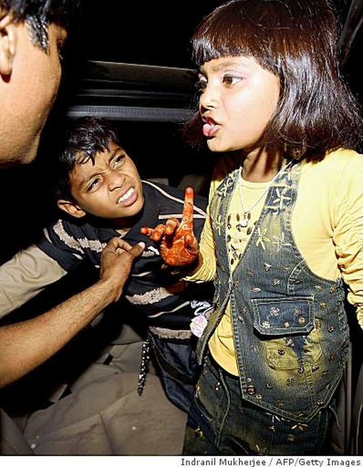"""Slumdog Millionaire"" child actor Mohammed Azharuddin Ismail (C) looks on as co-actor Rubina Ali speaks to an unidentified escort before leaving for the airport to catch a flight for the US to attend the Oscars ceremony, in Mumbai on February 20, 2009. ""Slumdog Millionaire"", the rags-to-riches tale of a Mumbai tea boy who wins big -nominated for 10 Oscars has already swept the board with four Golden Globe and seven British Academy Film Awards (BAFTAs) including best film. The Oscar-nominated film ""Slumdog Millionaire"" has been a hit in Indian city multiplexes since it opened here last month. Indian gamblers are staking big money on ""Slumdog Millionaire"" winning the best picture, best director and best music awards at this year's Oscars, a report said.  AFP PHOTO/INDRANIL MUKHERJEE (Photo credit should read INDRANIL MUKHERJEE/AFP/Getty Images) Photo: Indranil Mukherjee, AFP/Getty Images"