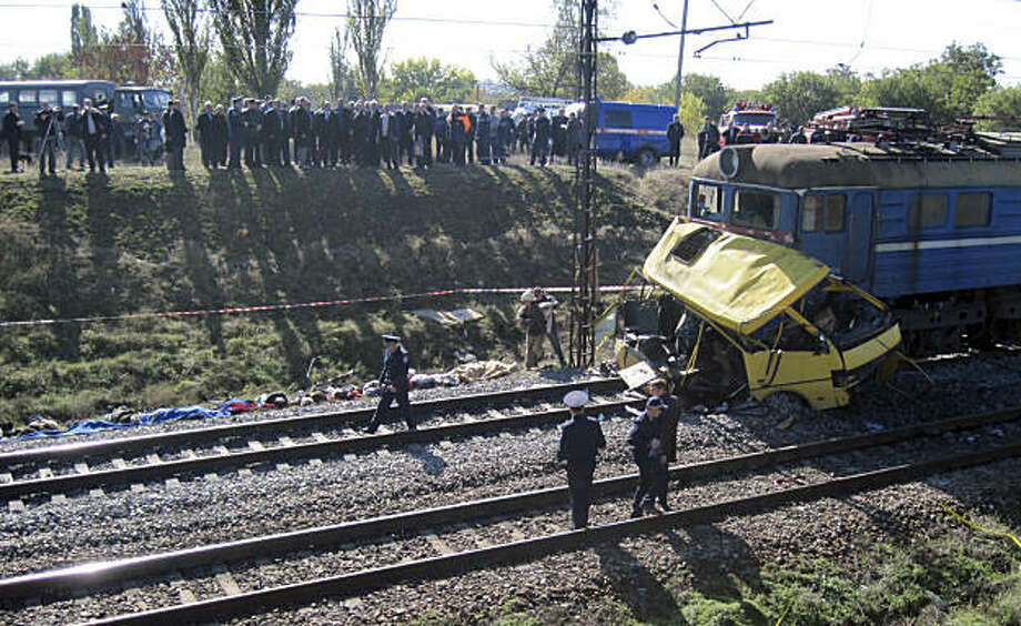 The remains of a bus lay next to a railway train at the site of an accident outside the town of Marhanets, Ukraine, Tuesday, Oct. 12, 2010. the crowded passenger bus collided with a train in eastern Ukraine Tuesday, killing 40 people and leaving 11 in critical condition, police said. The Interior Ministry said that the collision occurred outside the town of Marhanets in the Dnipropetrovsk region after the bus attempted to cross the track, ignoring a siren that indicated an oncoming train.Thirty-seven people from the bus died on the spot and another person died later in the hospital. There were no injuries reported on the train. Photo: AP