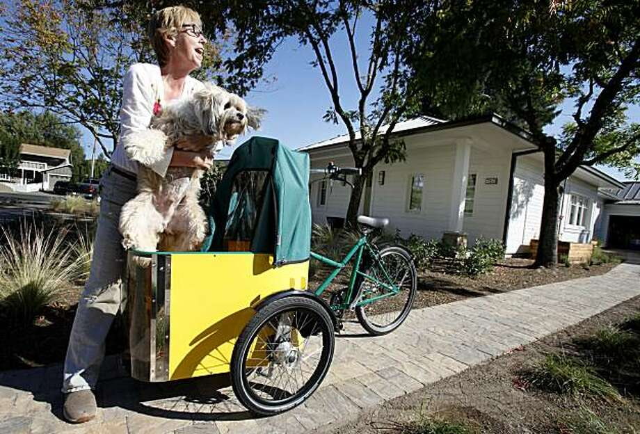 "Cathy O'Neill, the home owner, puts her dog Max O'Neill into the special dog carrier she has on her bike Thursday October 14, 2010. California's first ""passive"" home is a 2400 square foot masterpiece in Sonoma, Calif. The home uses a design popular in Europe which reduces energy consumption by 90 percent. Photo: Brant Ward, The Chronicle"