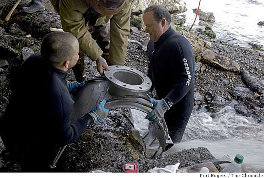 Dallas Leighton (left) and Tim Gulley place a valve over the pipe with the hole in it to try to stop the leak at the Sausalito-Marin City Sanitary District Fort Baker treatment plant, which is south of the city of Sausalito, on Wednesday, Feb 18,  2009. Photo: Kurt Rogers, The Chronicle