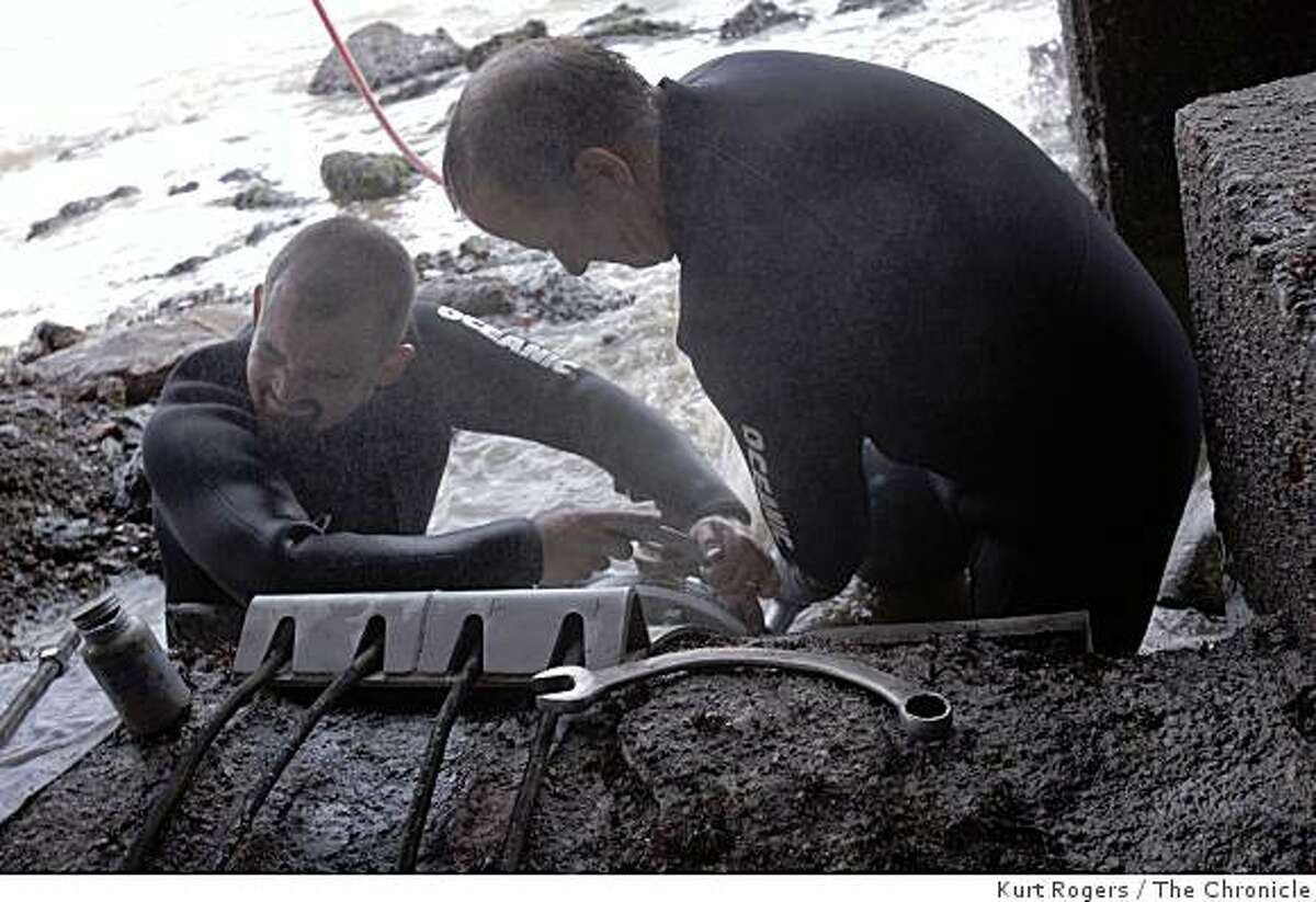 Dallas Leighton (left) and Tim Gulley tighten the bolts on the valve that was put on the pipe in order to stop the leak at the Sausalito-Marin City Sanitary District Fort Baker treatment plant on Wednesday, Feb 18, 2009 in Sausalito, Calif.