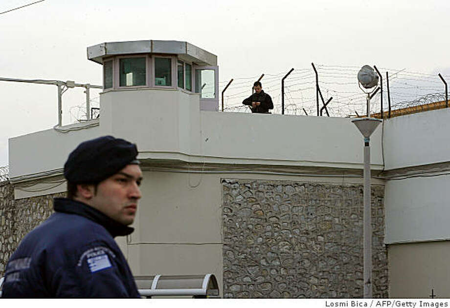Police guard the area around the Korydallos prison, near Athens, after Greece's most famous criminal, Vassilis Paleocostas, and an Albanian accomplice, Alket Rizai, escaped by helicopter from a maximum security prison in Athens, on February 22, 2009, acoording to a police source.  AFP PHOTO / Losmi Bica (Photo credit should read Losmi Bica/AFP/Getty Images) Photo: Losmi Bica, AFP/Getty Images