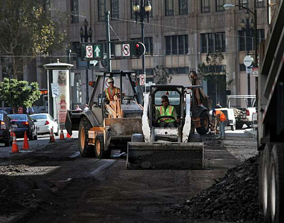 Workers with Esquivel Grading and Paving work on a repaving project on Fell Street between Franklin and Polk Streets on Tuesday Oct. 5, 2010 in San Francisco, Calif.