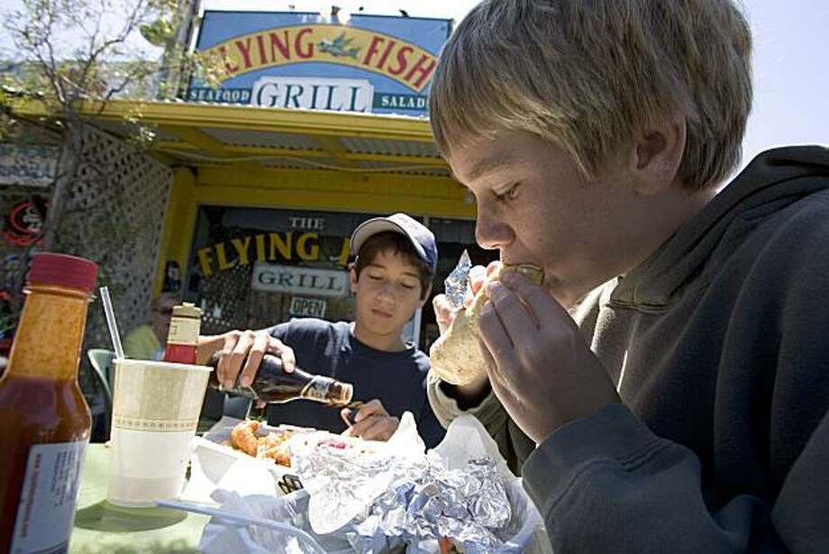 Two young diners dig into their fish tacos at Flying Fish Grill in Half Moon Bay. Photo: David Paul Morris, San Francisco Chronicle