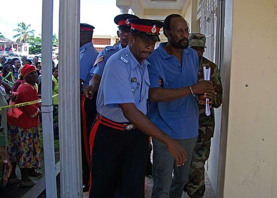 In this photo taken Sept. 7, 2010, Grenada's Ronald Michael Phillip, aka Ronald de Ally, second right, is escorted by police officers to the Sauteurs Magistrate Court in St. Patrick, Grenada. Phillip, a convicted felon in the U.S. who had been deported tohis Caribbean homeland, is the suspect in the murder of his landlord and nightclub owner, whose body was found Sept. 5 hacked with a machete. Photo: Johnson Richardson, AP