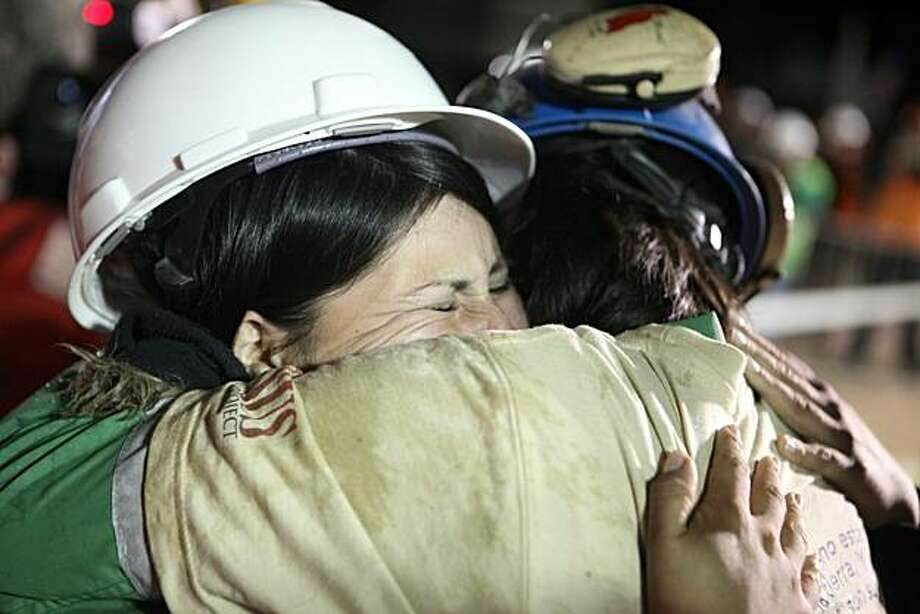 SAN JOSE MINE, CHILE - OCTOBER 13: (NO SALES, NO ARCHIVE) In this handout from the Chilean government,  Osman Araya, 29, is hugged by a relative as he becomes the sixth miner to exit the rescue capsule, on October 13, 2010 at the San Jose mine near Copiapo, Chile. The rescue operation has begun bringing up the 33 miners, 69 days after the August 5, 2010 collapse that trapped them half a mile underground. Photo: Handout, Getty Images