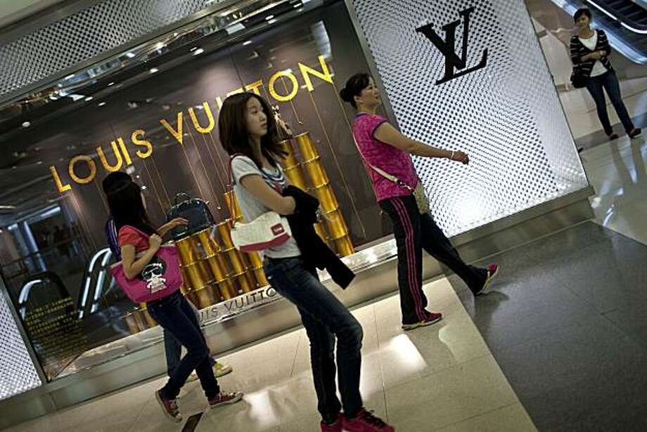 In this photo taken Thursday, Sept. 23, 2010, women walk past a Louis Vuitton store at a luxury shopping center in downtown Beijing. China, now the world's second largest economy, spent tens of billions of dollars on a dazzling Beijing Olympics in 2008 and has sent astronauts into space. Yet it also remains a major recipient of foreign aid, a fact that a growing number of taxpayers and lawmakers in donor countries are questioning. Photo: Alexander F. Yuan, AP