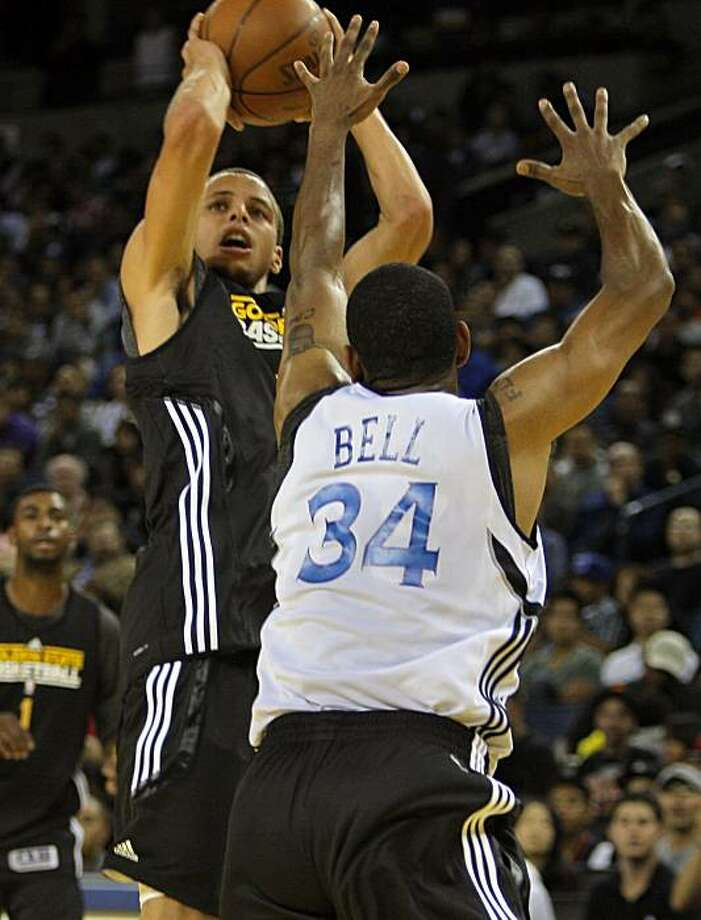 Stephen Curry, 30, makes a jumper over Charlie Bell, 34, during an open practice at Oracle Arena Wednesday, October 6, 2010, Oakland, Calif.  As the new season is set to begging the Golden State Warriors introduce new players and a largely new coaching staff to their fans. Photo: Adm Golub, The Chronicle