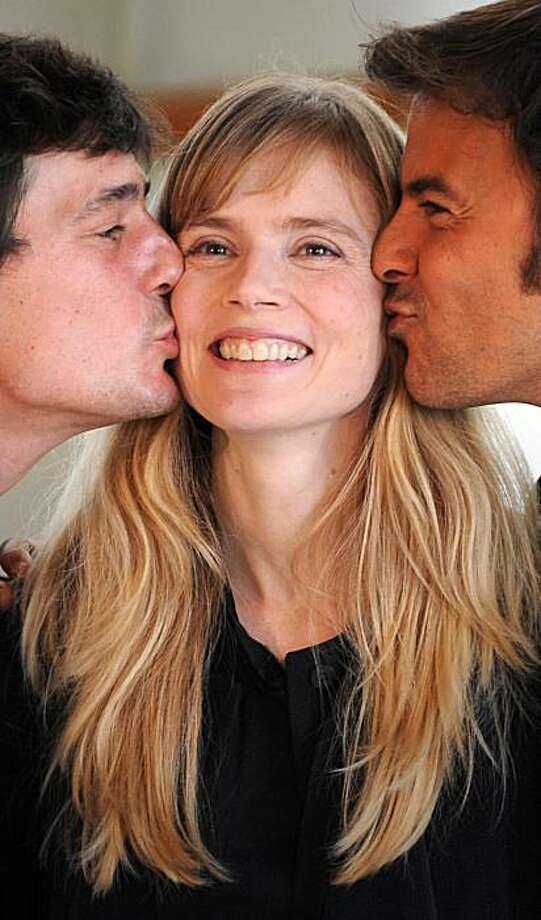 "French actress Isabelle Carre (C) is kissed by French director Francois Ozon (R) and French actor Louis-Ronan Choisy (L) during a photocall after the screening of Ozon's film ""Le Refuge"" (The Refuge) during the second day of the 57th San Sebastian International Film Festival, on September 19, 2009 in San Sebastian. Photo: Rafa Rivas, AFP/Getty Images"