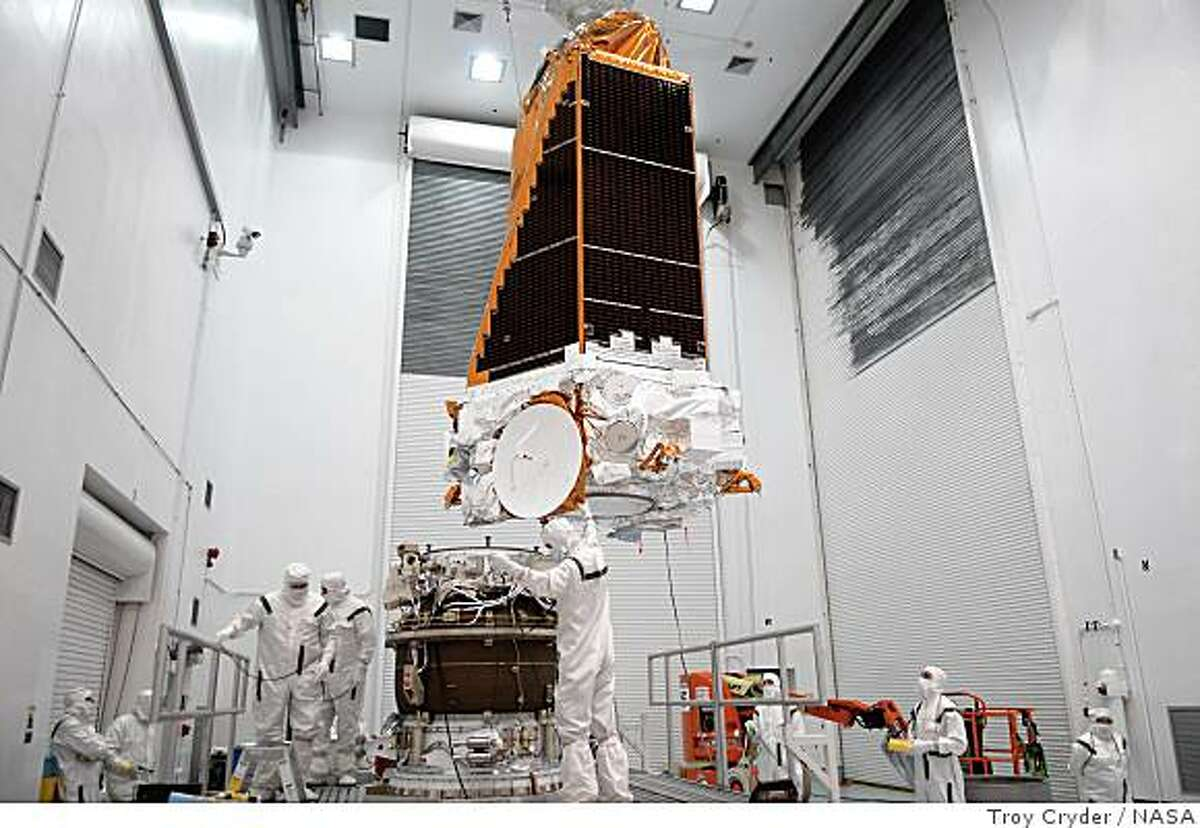 At the Hazardous Processing Facility at Astrotech in Titusville, Fla., workers guide the suspended Kepler spacecraft toward a Delta II third stage behind them, at left. Kepler is designed to survey more than 100,000 stars in our galaxy to determine the number of sun-like stars that have Earth-size and larger planets, including those that lie in a star's