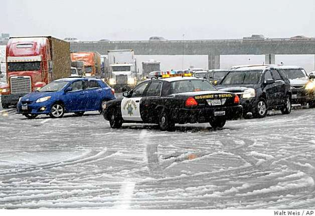 A Californa Highway Patrol car turns traffic around on Interstate I-15 as snow conditions forced the highway to be closed in the Cajon Pass in San Bernardino County, Calif. on Monday Feb. 16, 2009. A winter storm that could be the largest of the season blanketed California with heavy rain and snow on Monday, forcing the closure of a major highway and the cancellation of the final round of a national golf tournament.  (AP Photo/Walt Weis) Photo: Walt Weis, AP