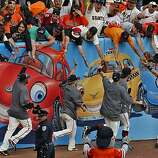 The Giants run around the stadium to celebrate with the crowd after winning the N.L. West Championship on Sunday.