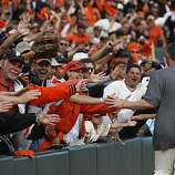 Aubrey Huff runs past excited fans after the San Francisco Giants win the NL West title at AT&T Park on Sunday.