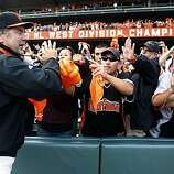 Giants manager Bruce Bochy celebrates the NL West title with fans at AT&T Park on Sunday.