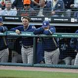 Players and coaches in the San Diego Padres dugout look grim as the San Francisco Giants celebrate a 3-0 win and the NL West title at AT&T Park on Sunday.
