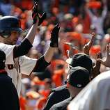 Jonathan Sanchez is greeted in the dugout after scoring the Giants' first run following his third inning triple against the San Diego Padres at AT&T Park on Sunday.