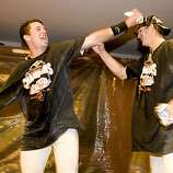 Buster Posey and Matt Cain shower each other with beer as the San Francisco Giants celebrate their  National League West Championship after defeating the San Diego Padres at AT&T Park on Sunday.