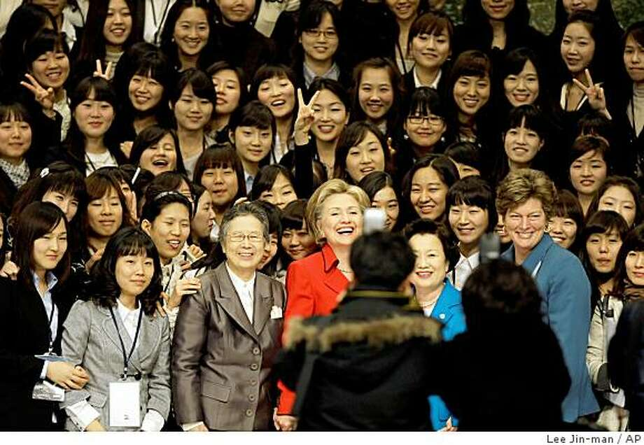 U.S. Secretary of State Hillary Rodham Clinton, center, poses for photos with students and officials after a meeting with them at Ewha Womans University in Seoul, South Korea, Friday, Feb. 20, 2009. Clinton named a special envoy for North Korea on Friday but warned the communist nation that ties with the United States will not improve unless it stops threatening South Korea. (AP Photo/ Lee Jin-man) Photo: Lee Jin-man, AP
