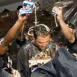 Pat Burrell is showered with beer by teammates as the Giants celebrate their division championship after defeating the San Diego Padres at AT&T Park on Sunday.