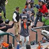 The Giants celebrate as they run into the dugout after winning the NL West title Sunday.