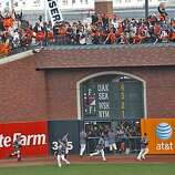 The Giants run around the field to celebrate after winning the NL West title against the San Diego Padres on Sunday.