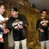 Eli Whiteside plays with his son, Whit, held by Amy Whiteside, Eli's wife, as Buster Posey and his wife laugh in the locker room at AT&T Park on Sunday.