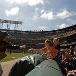 """Ball Dudet"" Sandy Antony hands a foul ball to Grace Broberg, 11, of San Jose as the San Francisco Giants take on the San Diego Padres at AT&T Park on Sunday."