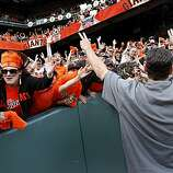 The Giants' Pat Burrell makes his way through the fans after the victory Sunday.