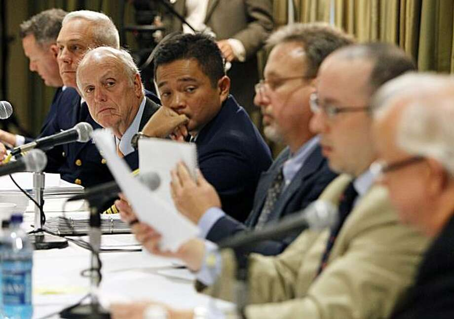 Deepwater Horizon joint investigation board members, from the left, U.S. Coast Guard Lt. Robert Butts, Capt. Mark Higgins, Wayne Andersen, U.S. District Judge (Ret.), Capt. Hung Nguyen, David Dykes, Jason Mathews and John McCarroll look through documentsduring testimony from BP PLC Nick Wilson, not pictured, during joint investigation hearings held by the U.S. Coast Guard and the Bureau of Ocean Management Regulation and Enforcement in Metairie, La., Wednesday, Oct. 6, 2010. Photo: Patrick Semansky, AP