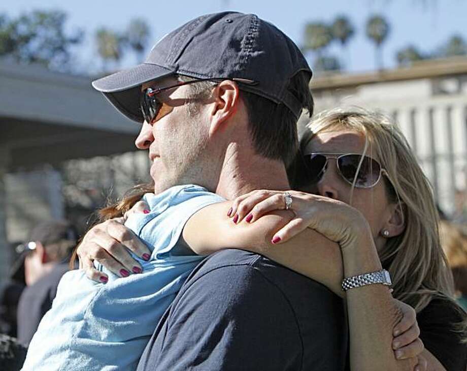 A mother and father hug their daughter at Kelly Elementary School where a gunman wounded two children after opening fire Friday, Oct. 8, 2010, in Carlsbad, Calif. Photo: Lenny Ignelzi, AP
