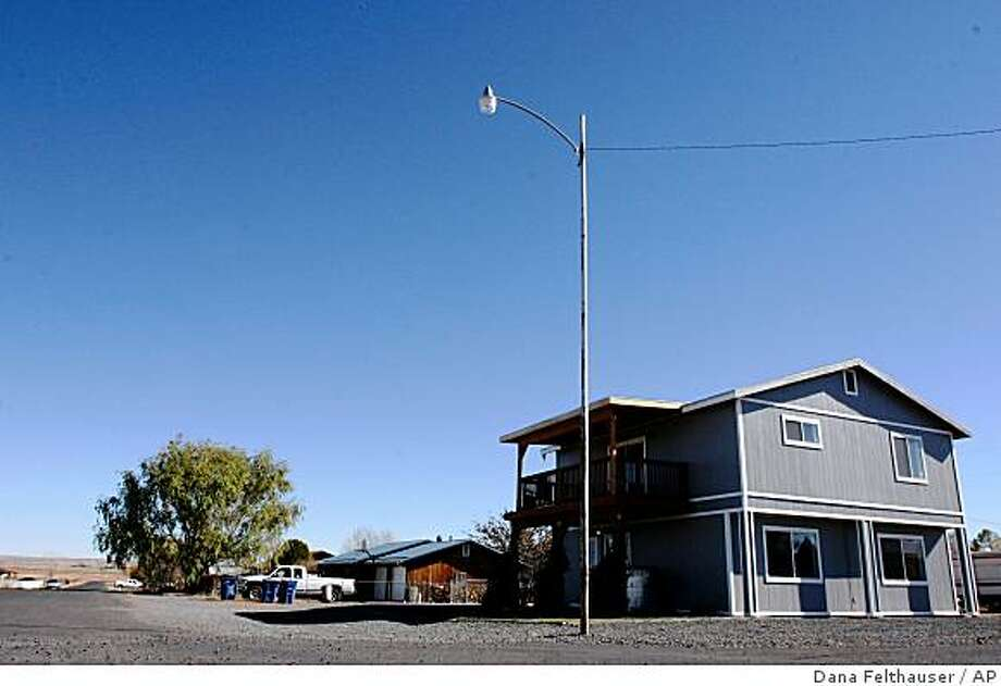 ** FILE ** This Nov. 8, 2008 file photo shows the house in St. Johns, Ariz. where Vincent Romero, 29, and Timothy Romans, 39, of San Carlos, Ariz. were found fatally shot. Police said Romero's 9-year-old son, who was 8 at the time, used a .22-caliber rifle to shoot the men as they returned home from work. The eastern Arizona boy pleaded guilty Thursday to a single count of negligent homicide. (AP Photo/Dana Felthauser, File) Photo: Dana Felthauser, AP