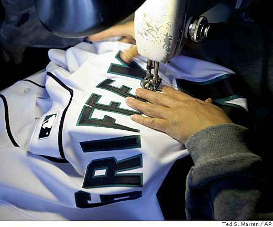 Patricia Lopez, a worker at STT Sports Lettering Co. in Seattle, sews Ken Griffey Jr.'s name onto a MLB baseball jersey Thursday, Feb. 19, 2009, in Seattle. The Mariners announced late Wednesday that Griffey, who played with the team from 1989 to 1999, would be returning to Seattle for the 2009 season. (AP Photo/Ted S. Warren) Photo: Ted S. Warren, AP