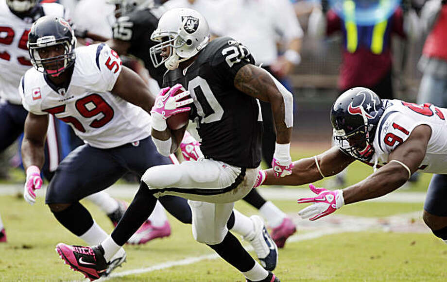 Oakland Raiders running back Darren McFadden (20) breaks up the middle past Houston Texans defensive tackle Amobi Okoye (91) and linebacker DeMeco Ryans during the first quarter of an NFL football game in Oakland, Calif., Sunday, Oct. 3, 2010. Photo: Ben Margot, AP