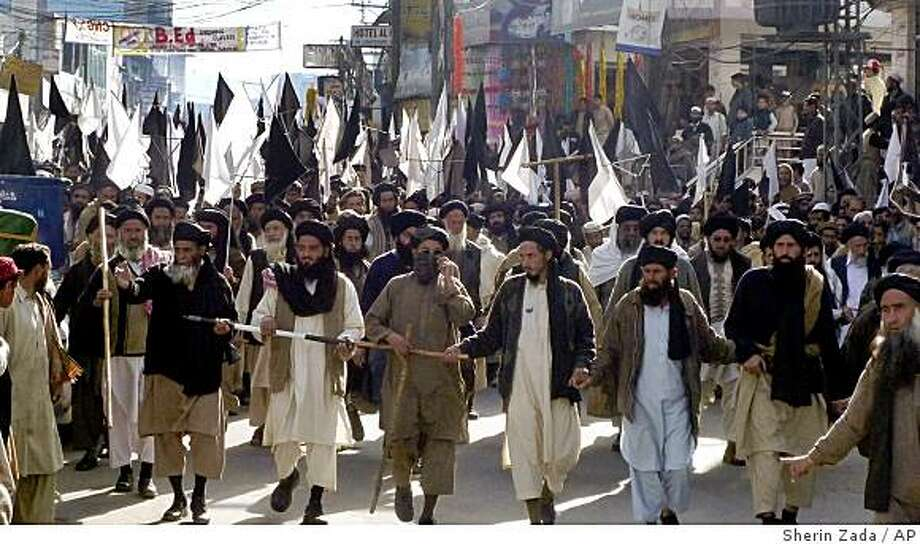 Supporters of  Pro-Taliban cleric Sufi Muhammad march in  Swat's main city of Mingora on Wednesday, Feb. 18, 2009 in Pakistan. A hardline cleric led hundreds of supporters in a peace march in Pakistan's Swat Valley on Wednesday aimed at convincing Taliban militants to lay down their weapons under a pact with the government. (AP Photo/Sherin Zada) Photo: Sherin Zada, AP