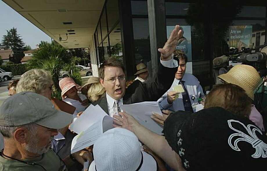 Robert Brown FDIC ombudsman distributes forms for people to fill out before getting their money back outside IndyMac Bank Tuesdau July 15, 2008, in Encino, Calif. Some 200 anxious, embittered and sometimes angry customers swarmed an IndyMac bank branch, Tuesday, creating a Depression Era-like scene in the city's San Fernando Valley, as they demanded their money back. (AP Photo/Nick Ut) Photo: Nick Ut, AP