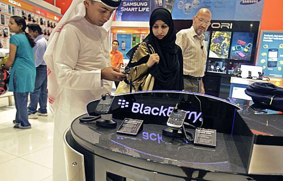 An Emirati couple at the Blackberry stand, at a mobile phone dealer shop in Dubai, United Arab Emirates, Friday Oct. 8, 2010. The United Arab Emirates on Friday backed off a threat to cut key BlackBerry services, just days before a planned ban that couldhave harmed the country's business-friendly reputation. The last-minute decision ended more than two months of brinksmanship we country's tough negotiating stance and its role as a highly wired, tech-savvy trade and transportation hub. Photo: Farhad Berahman, AP
