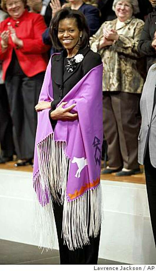 First Lady Michelle Obama models a handmade shawl she received from Director of Public Affairs for the Bureau of Indian Affairs Nedra Darling, onday, Feb. 9, 2009, during an event at the Interior Department  in Washington. (AP Photo/Lawrence Jackson) Photo: Lawrence Jackson, AP