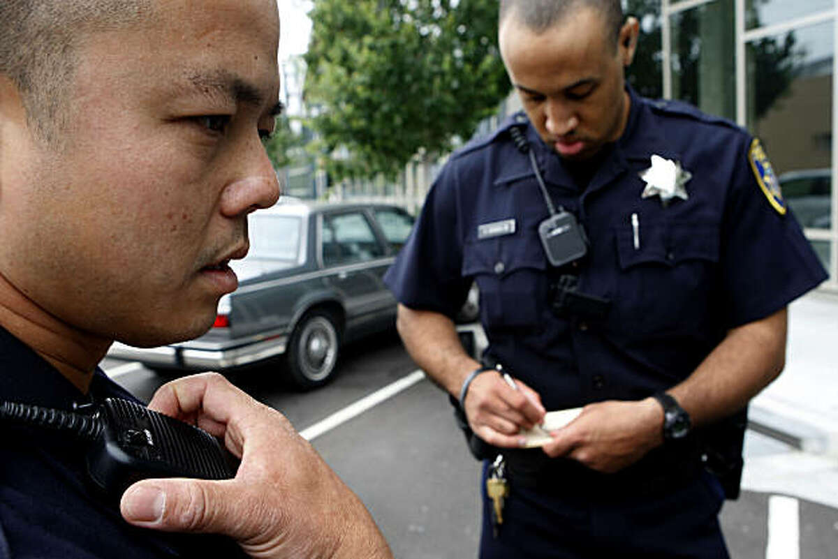 Officer Huy Nguyen (left) and Officer Anthony Banks, Jr. of the Oakland Police Department investigate a car that was broken in to near Jack London Square while on walking patrol during the farmer's market on Sunday, July 11, 2010 in Oakland, Calif. As of October 05, 2010 both Nguyen and Banks were still employed by OPD.