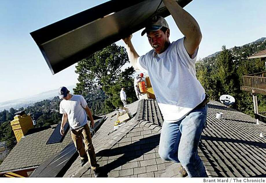 Solar installer Delmar Oliveira (right foreground) carried a panel to a new location on the roof. The solar industry has been a bright spot in a down economy. The Los Gatos based company Akeena Solar is installing 44 solar panels on a home in the Oakland hills Thursday January 15, 2008. Photo: Brant Ward, The Chronicle